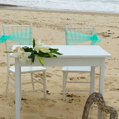 white table and two chairs on beach